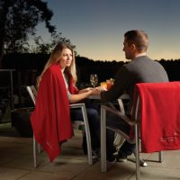 Couple enjoying dinner wrapped up in soft promo fleece blanket